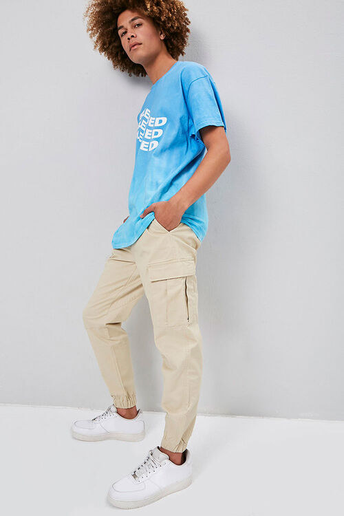 Model wears the khaki cargo pants with a blue tee and white sneakers