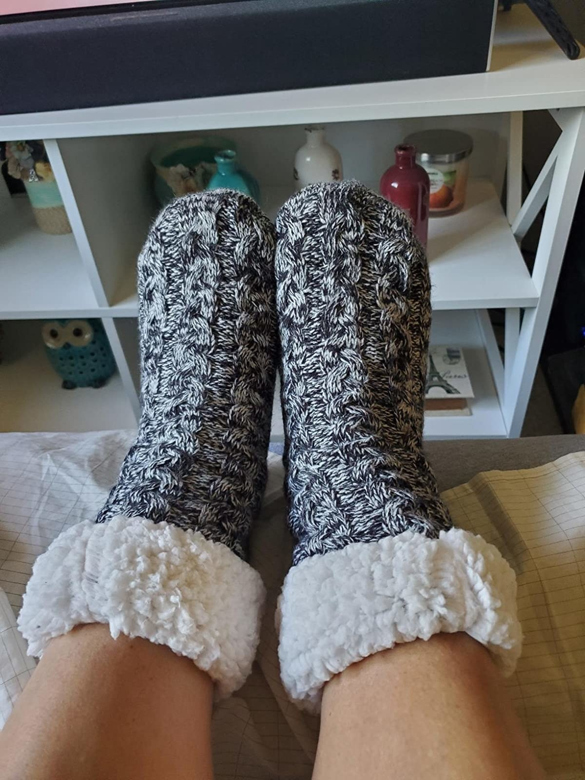 A reviewer wearing the socks in black and white