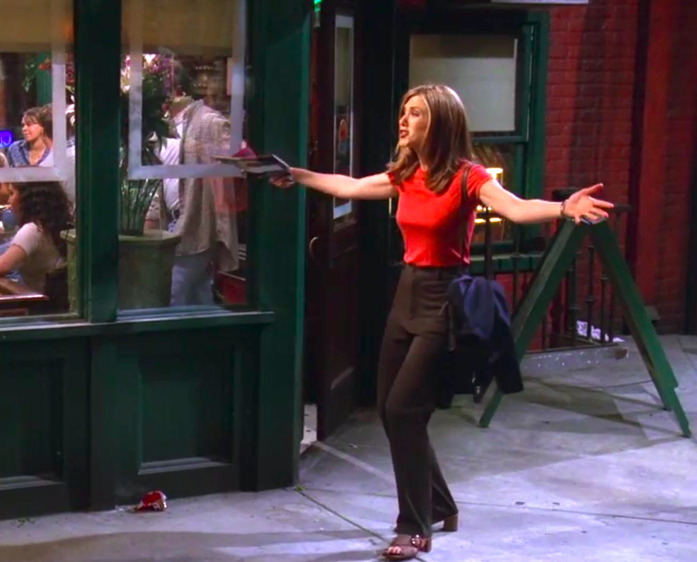 Rachel wearing slim pants, a red shirt, and a cute off-the-shoulder bag, but also weird sandal heels