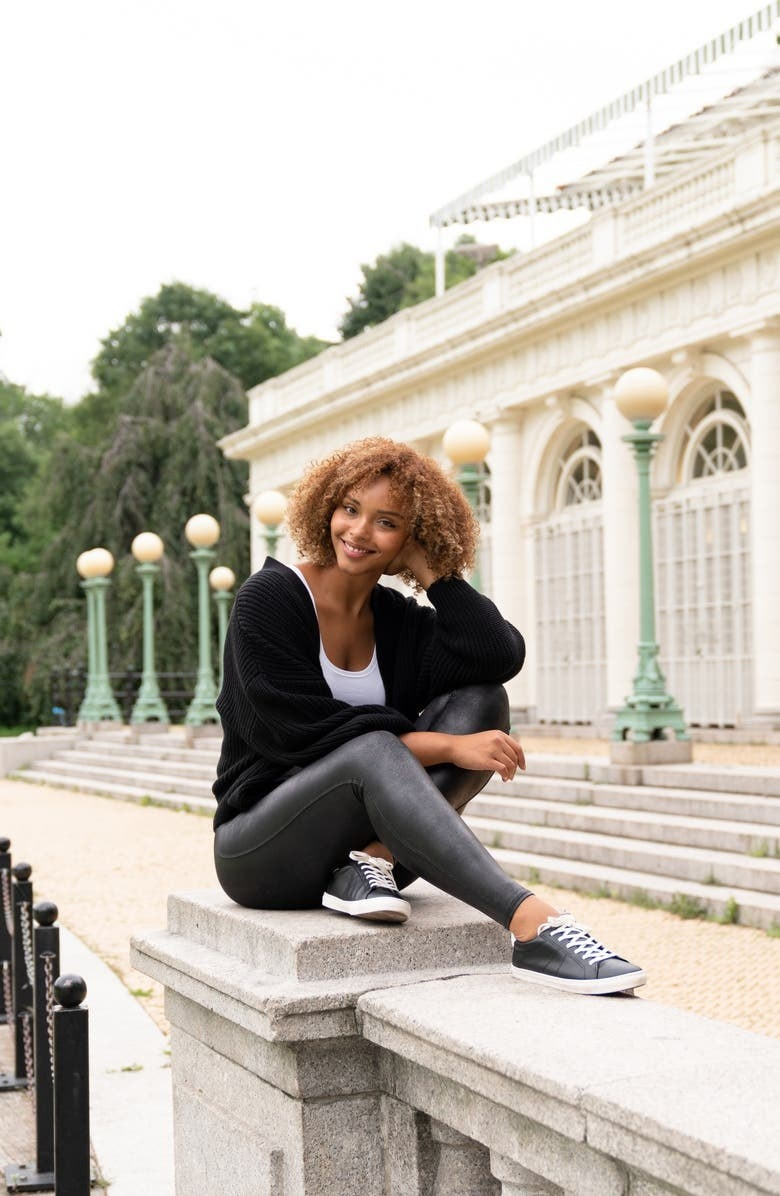 A model wearing the leggings and matching leather shoes while sitting on a railing