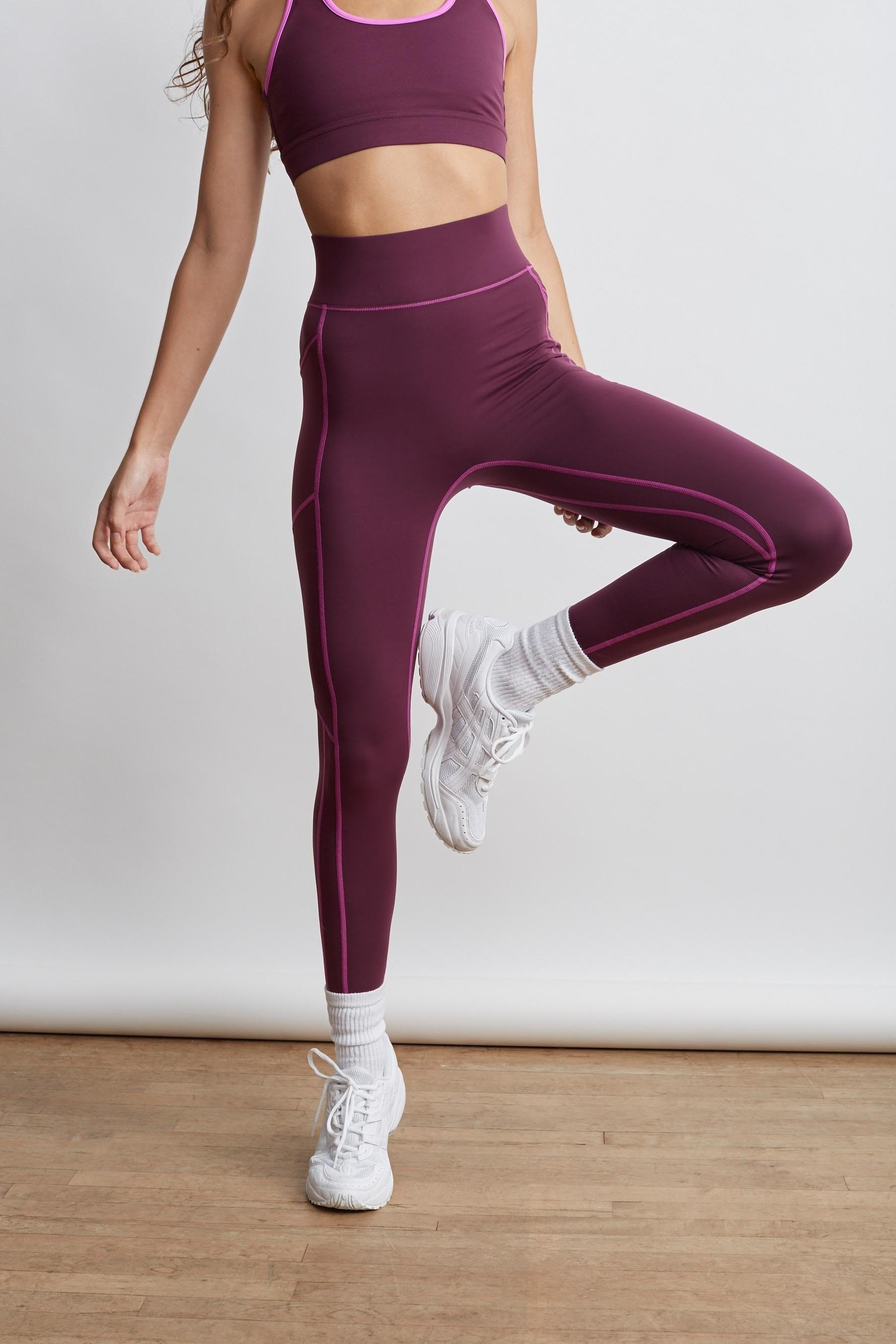 Model wears mulberry high-rise leggings with hot pink stitching on the legs, hips, and waist