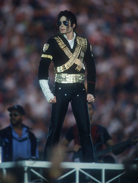 Michael Jackson posing in black suit with a gold X on the front