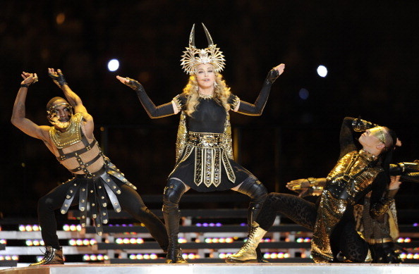 Madonna dancing in black and gold headpiece with two backup dancers