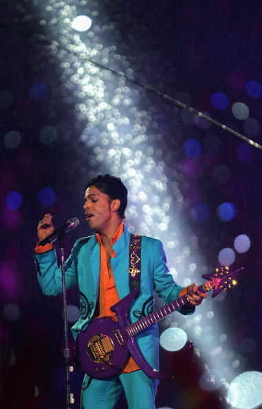 Prince singing into a microphone and holding a purple guitar