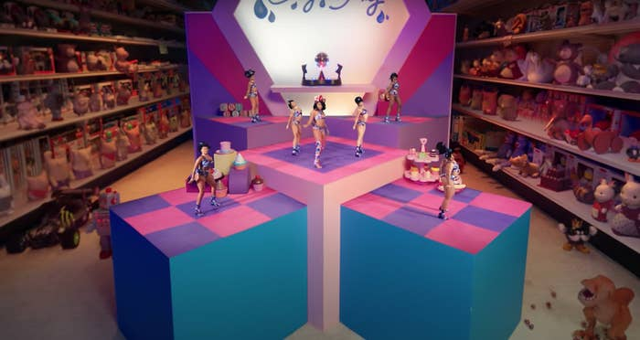 screenshot of megan thee stallion's music video for cry baby where there are miniature versions of each dancer inside a toy store