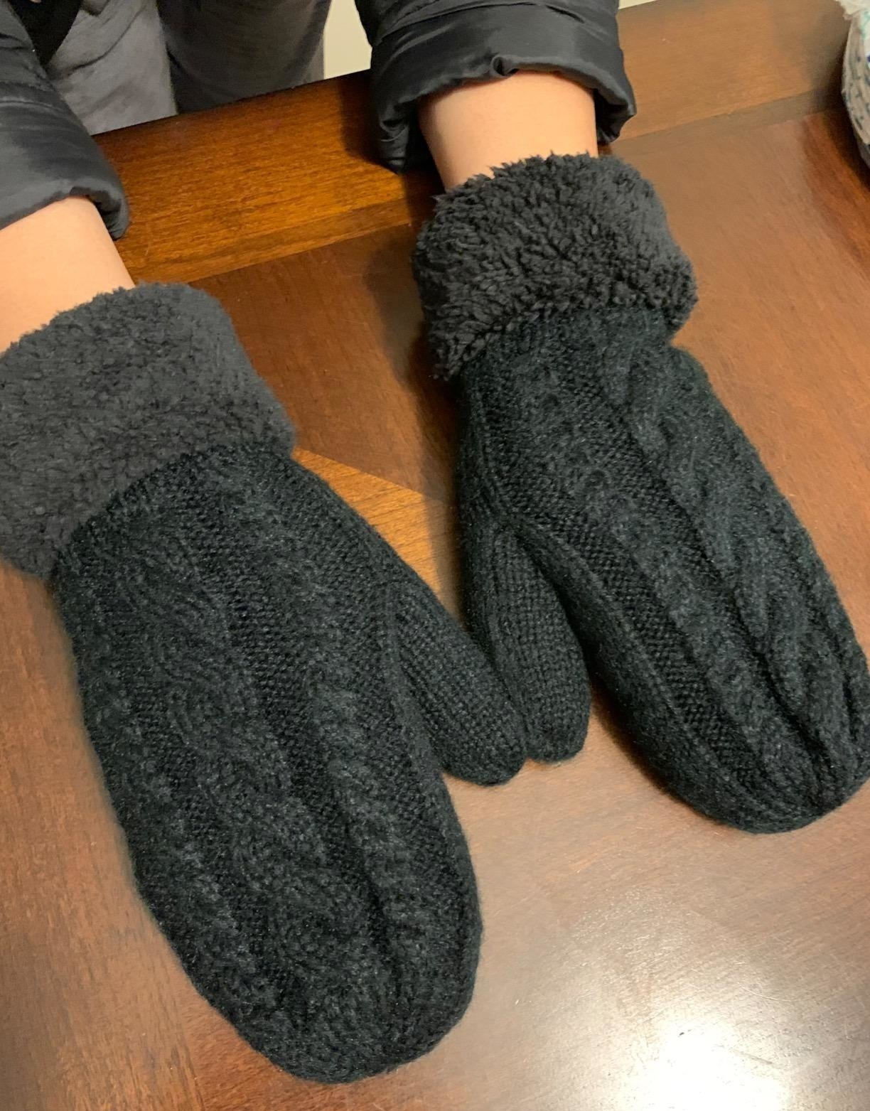 A reviewer wearing the mittens in black