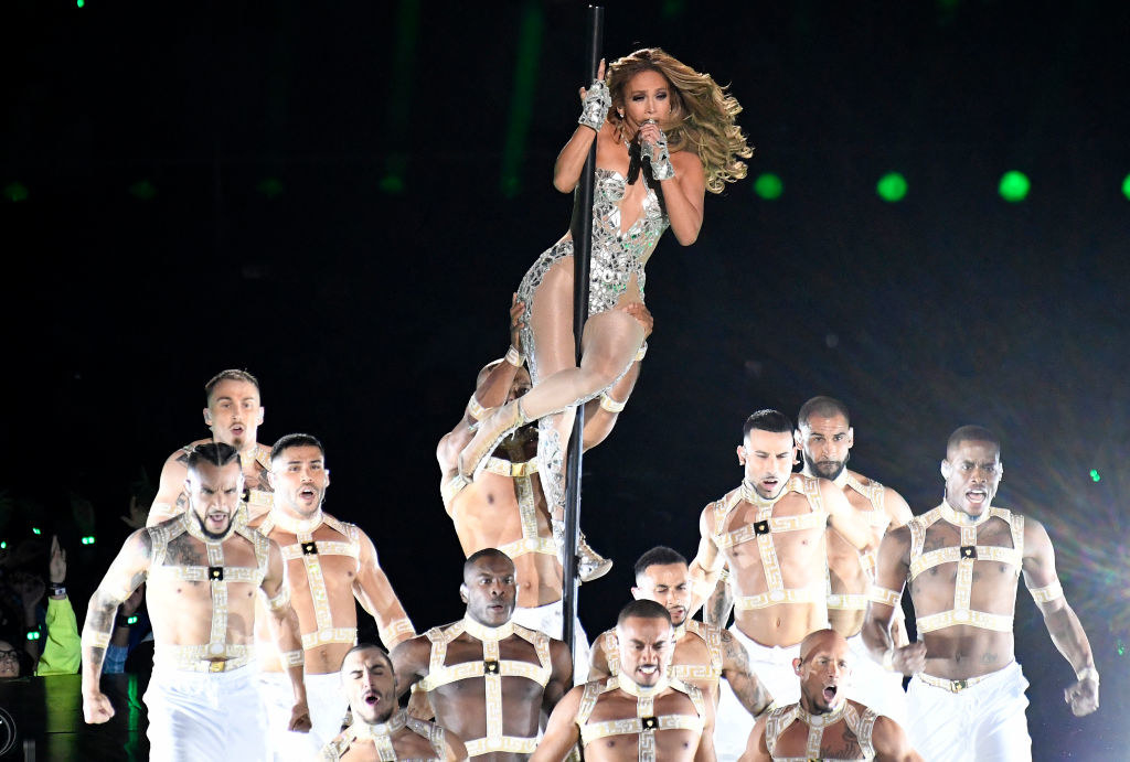 Jennifer Lopez wearing a diamond bodysuit and pole dancing with male backup dancers
