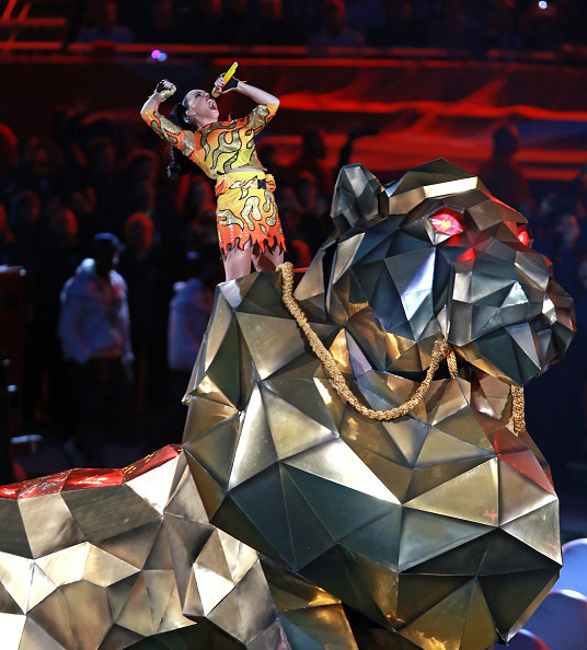 Katy Perry riding a giant pretend lion and singing