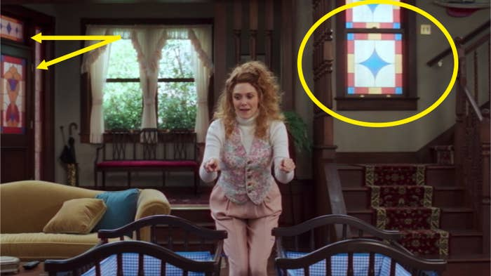 Wanda standing in her living and circles and arrows pointing out the stained glass on the door and near the stairs