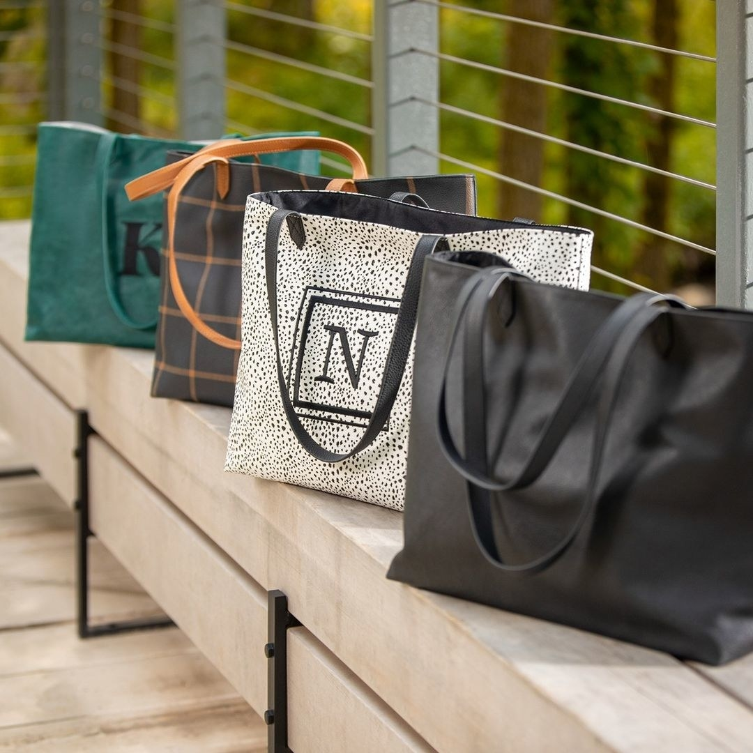 four spacious top-handle shoulder totes, some monogrammed; in black; in white with black dot print, in navy with brown windowpane print, and in teal