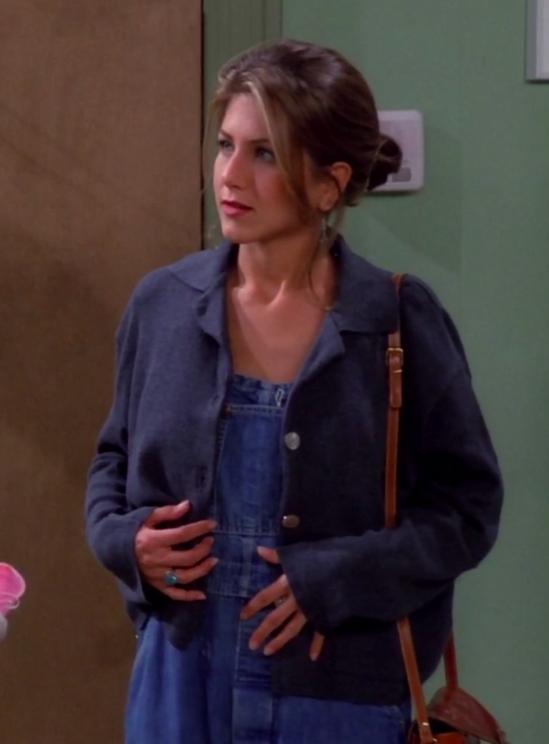 Rachel wearing a shoulder bag, a cardigan, and overalls