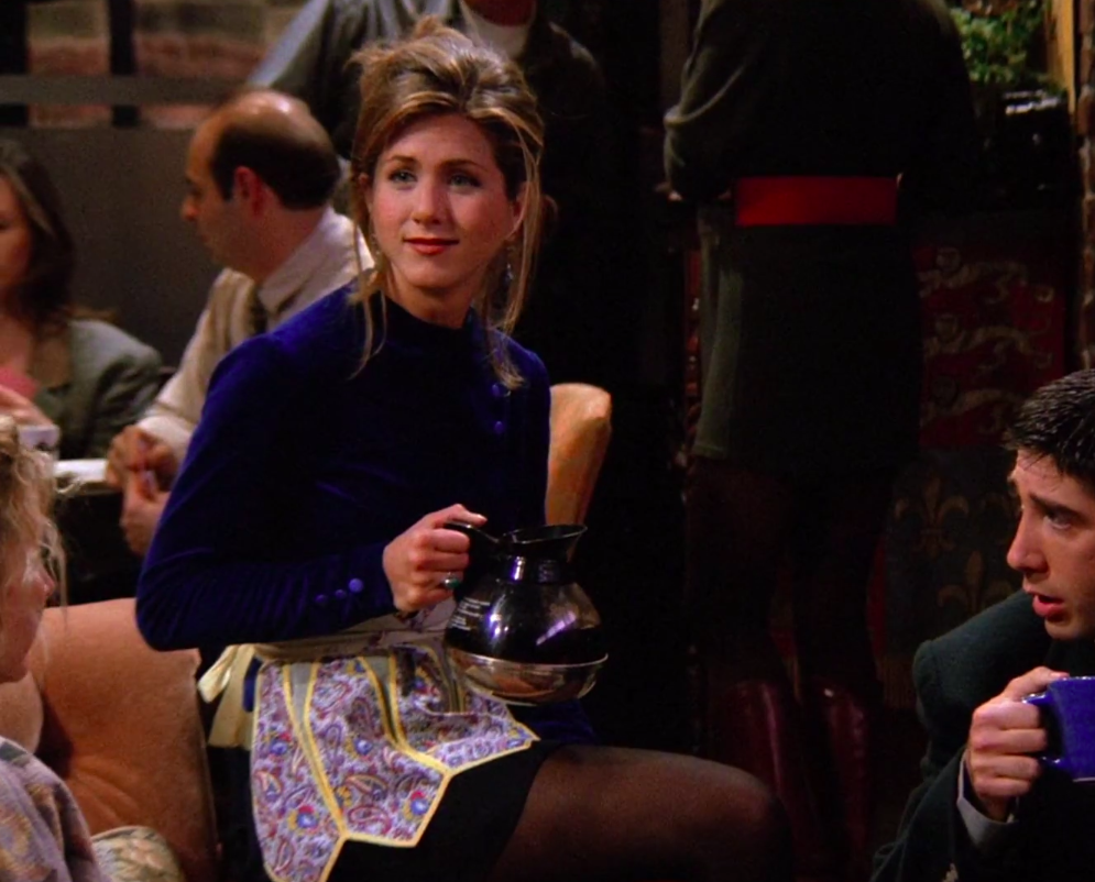 Rachel wearing a blue velvet shirt and a pretty apron over a black skirt