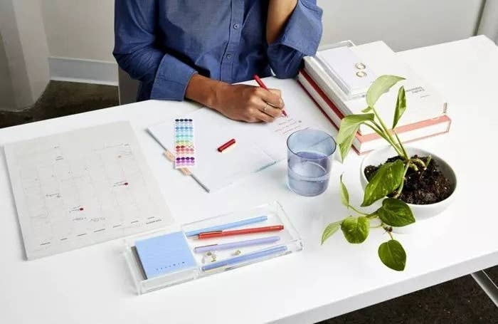 a model writing in a notebook next to the calendar pad