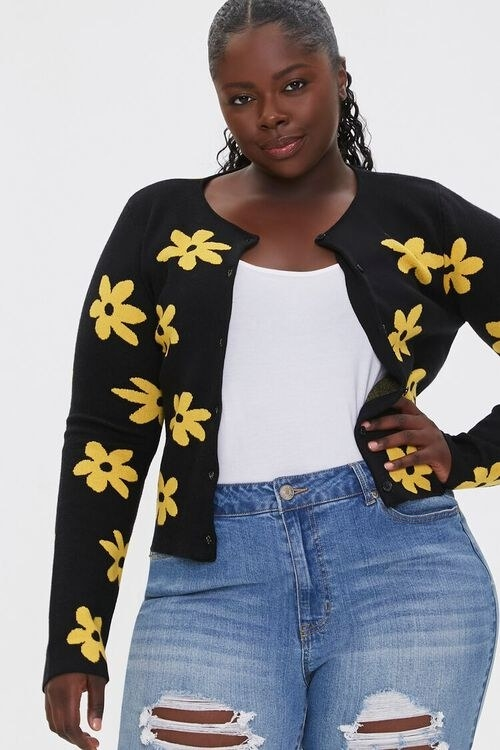 Model wears black cardigan with yellow flowers with a white top and midwash jeans
