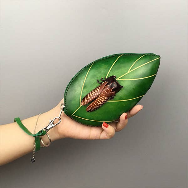 a hand holding the leaf clutch with a cicada bug in the center of it