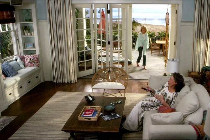 Grace and Frankie hang out on the couch near open doors that lead to the ocean