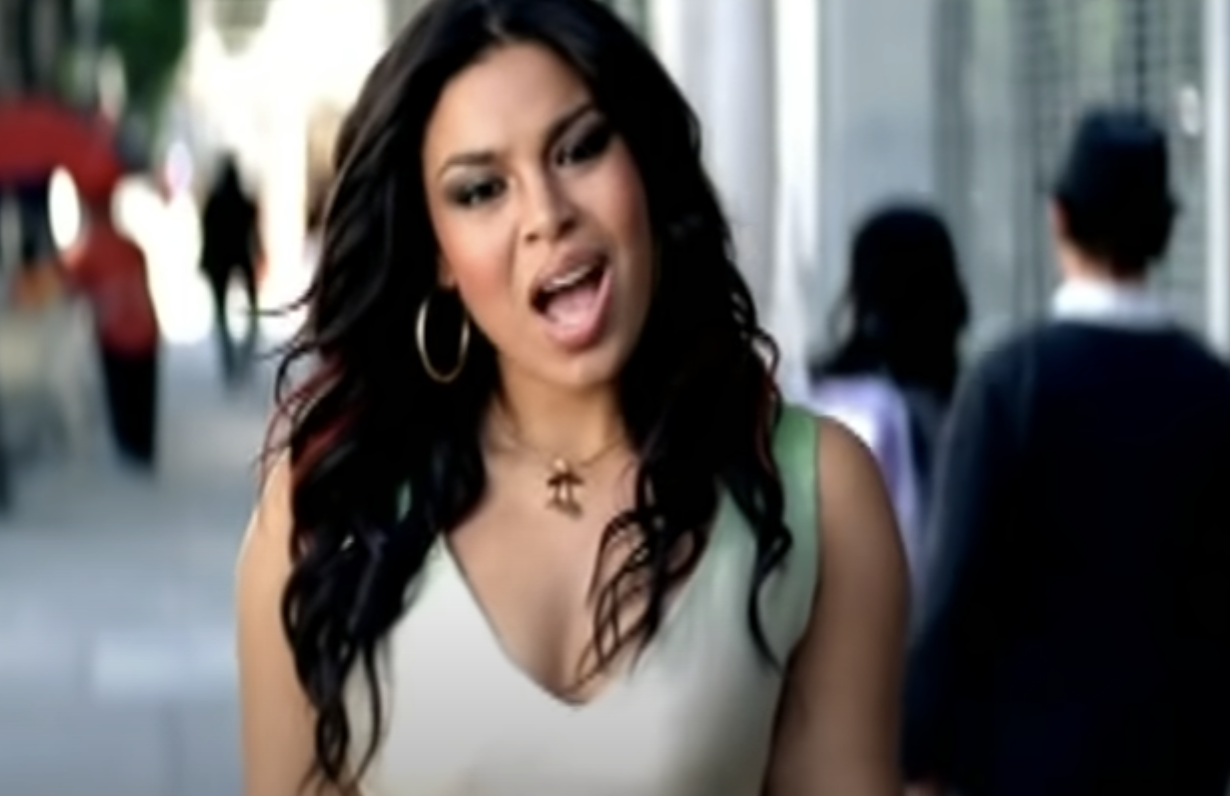"""Jordin walking down the street and singing in the """"One Step at a Time"""" video"""