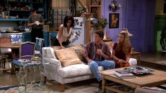 Joey in the kitchen while Monica, Phoebe, and Chandler gather around the couch in the living room