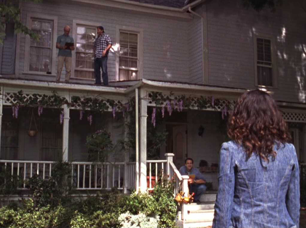 Lorelai stands in front of her home while Luke and construction workers work on the house