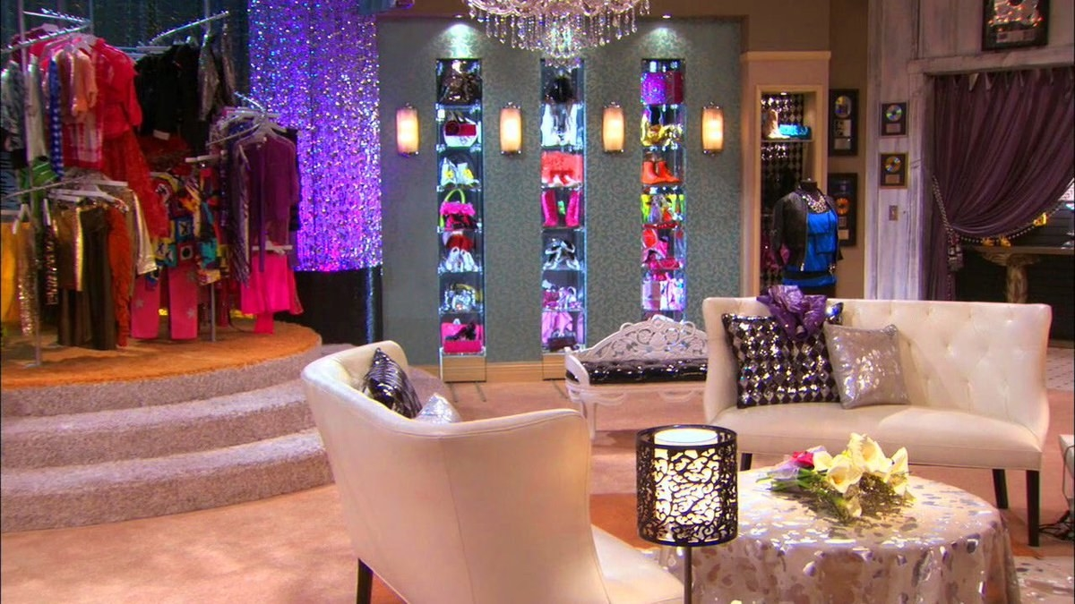 A large room with light carpeting, two chandeliers, a clothing carousel with bright clothes, and a wall of shoes. There are also cream-colored couches and a few blonde wigs.
