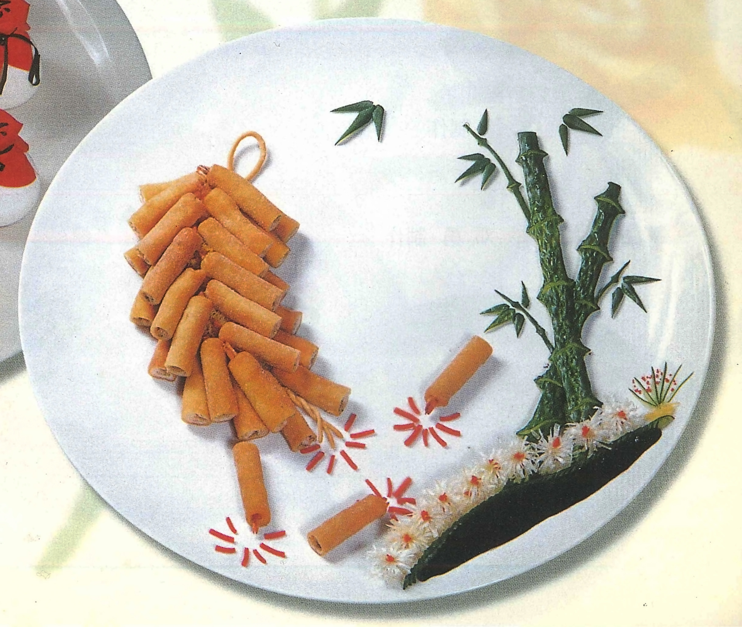 Spring rolls and bamboo are arranged on a plate to resemble Chinese fireworks and a landscape