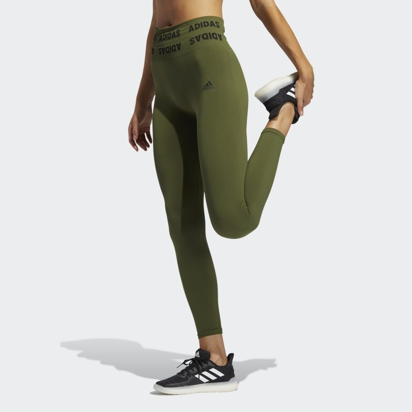 Model wears olive green Adidas high-rise leggings with black sneakers