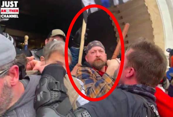 A red circle is drawn around the face of a man wielding a baton among a crowd