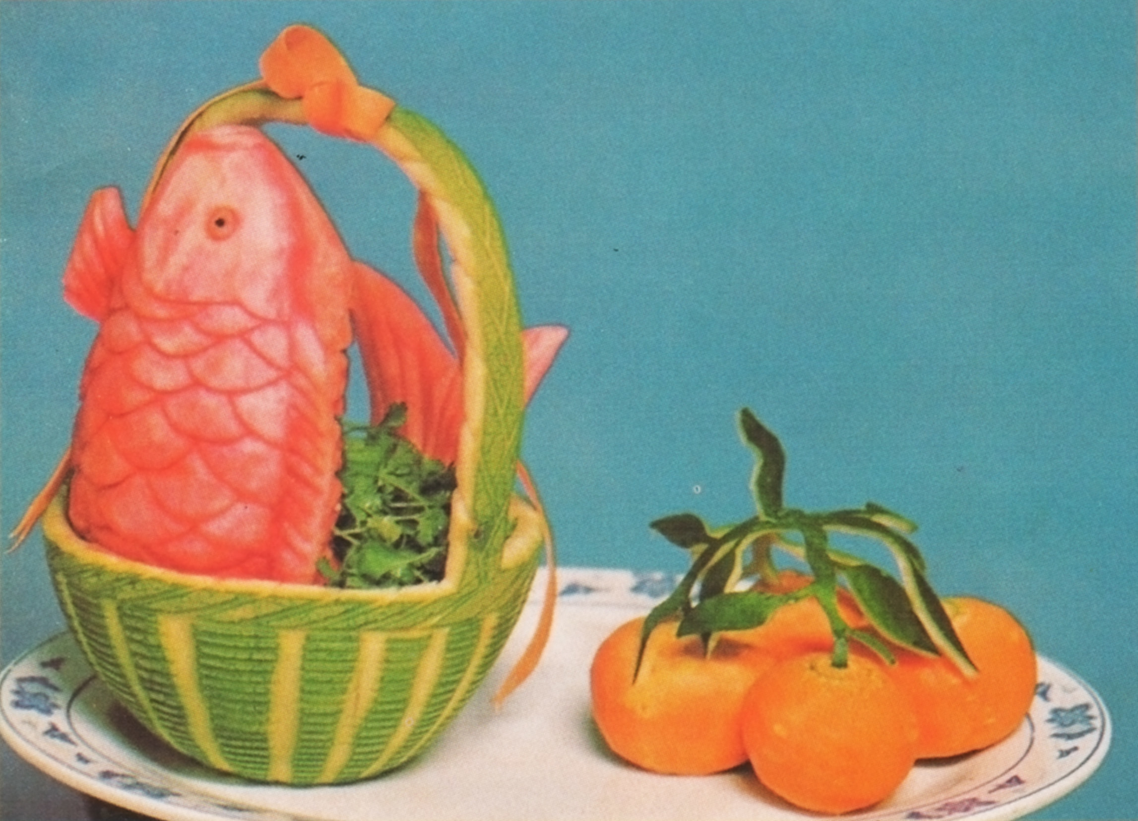 A fish in a basket made of  a carved gourd with oranges next to it on a plate