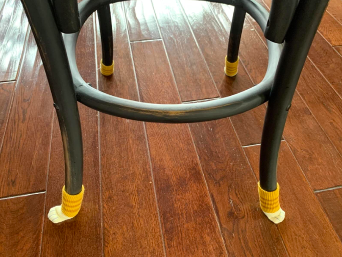 a reviewer photo of the orange cat paw furniture socks on a stool