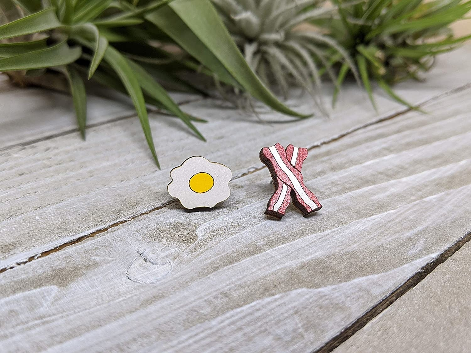 the fried egg and bacon earrings on a wooden table top