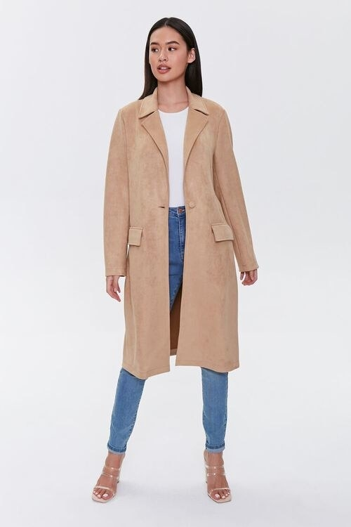 Model wearing camel colored duster with lapels and pockets