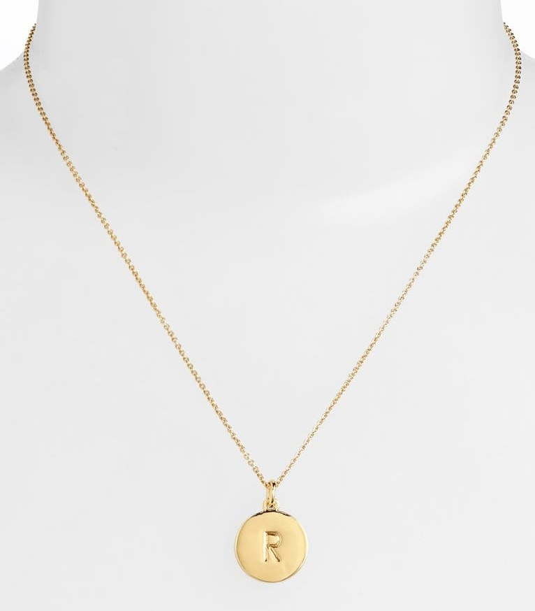 The pendant necklace, sporting the letter R