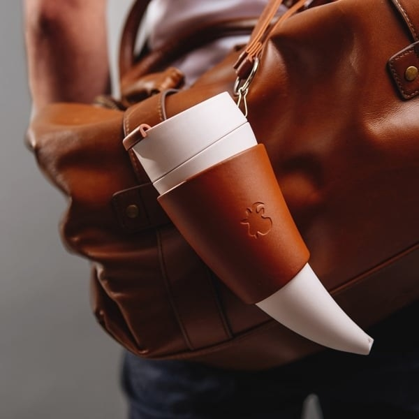 the goat-horn shaped coffee cup in a travel strap attached to a bag