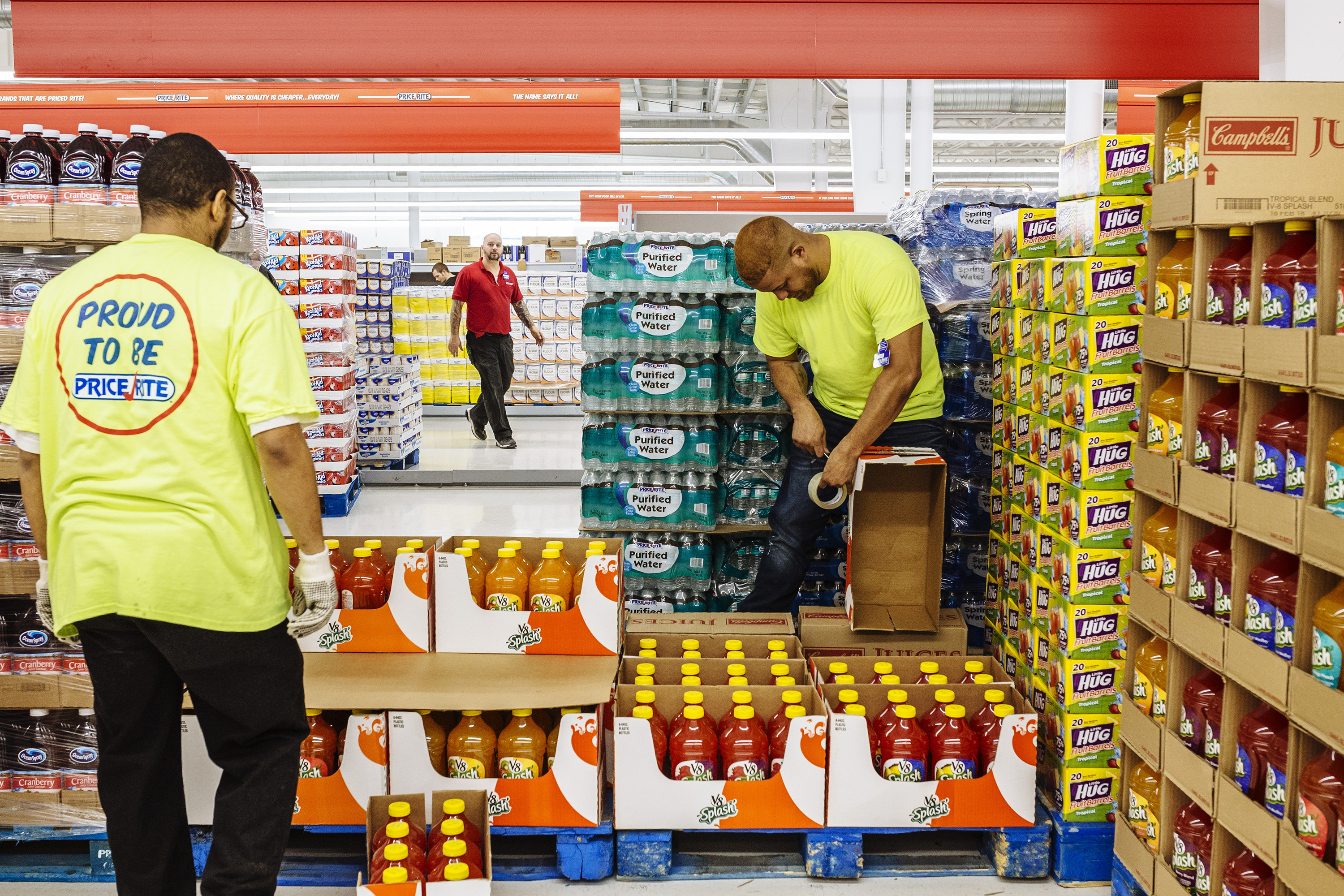Two men in neon Price Rite shirts set up a display of juice bottles inside the supermarket