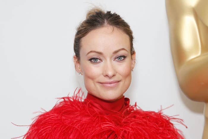 Olivia Wilde wearing a feathered outfit and her hair up in a bun