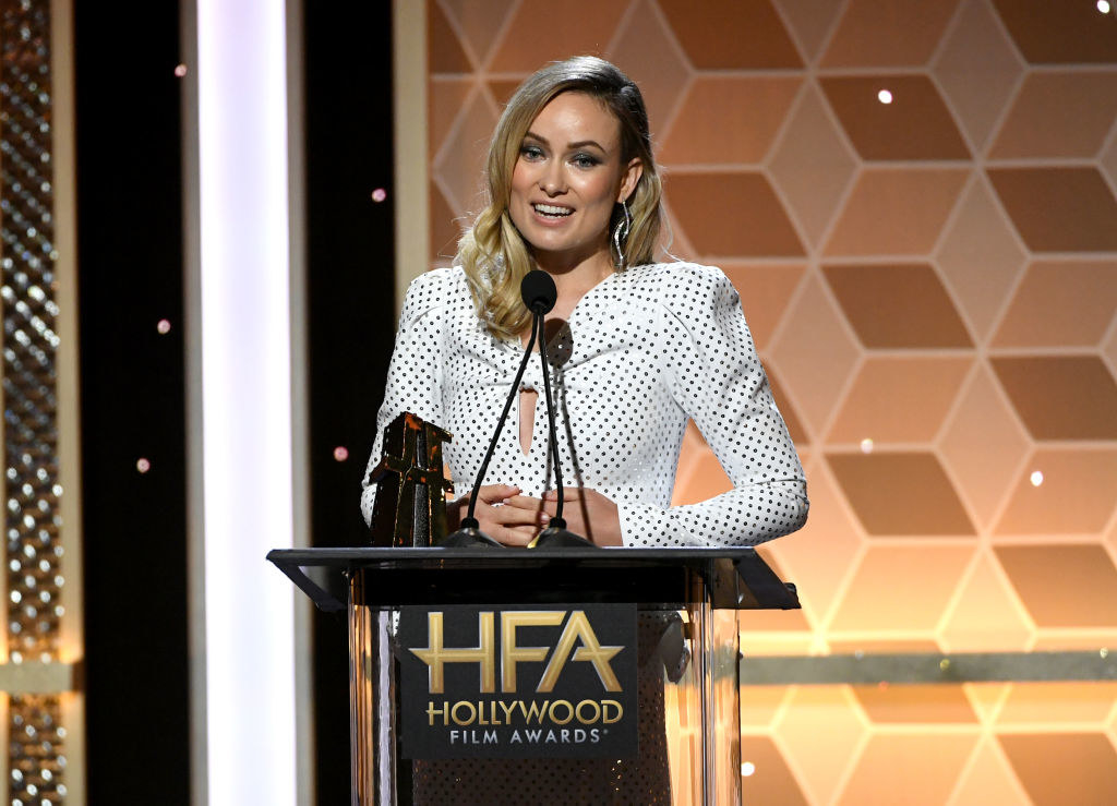Olivia Wilde wearing a patterned dress onstage at the Hollywood Film Awards