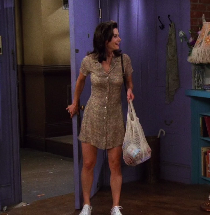 Monica wearing a button dress and sneakers