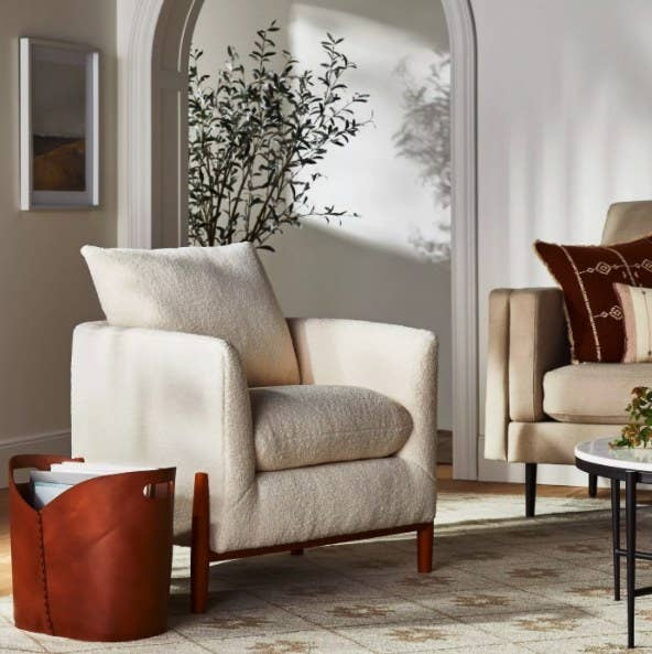 The cream sherpa chair with wood legs in a living room
