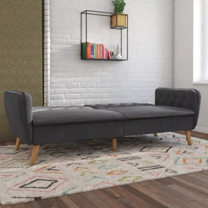 The futon in the color gray and turned down to show bed