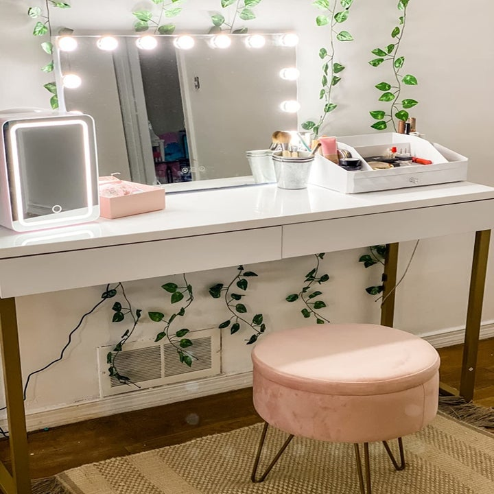 The pink ottoman in front of a makeup vanity