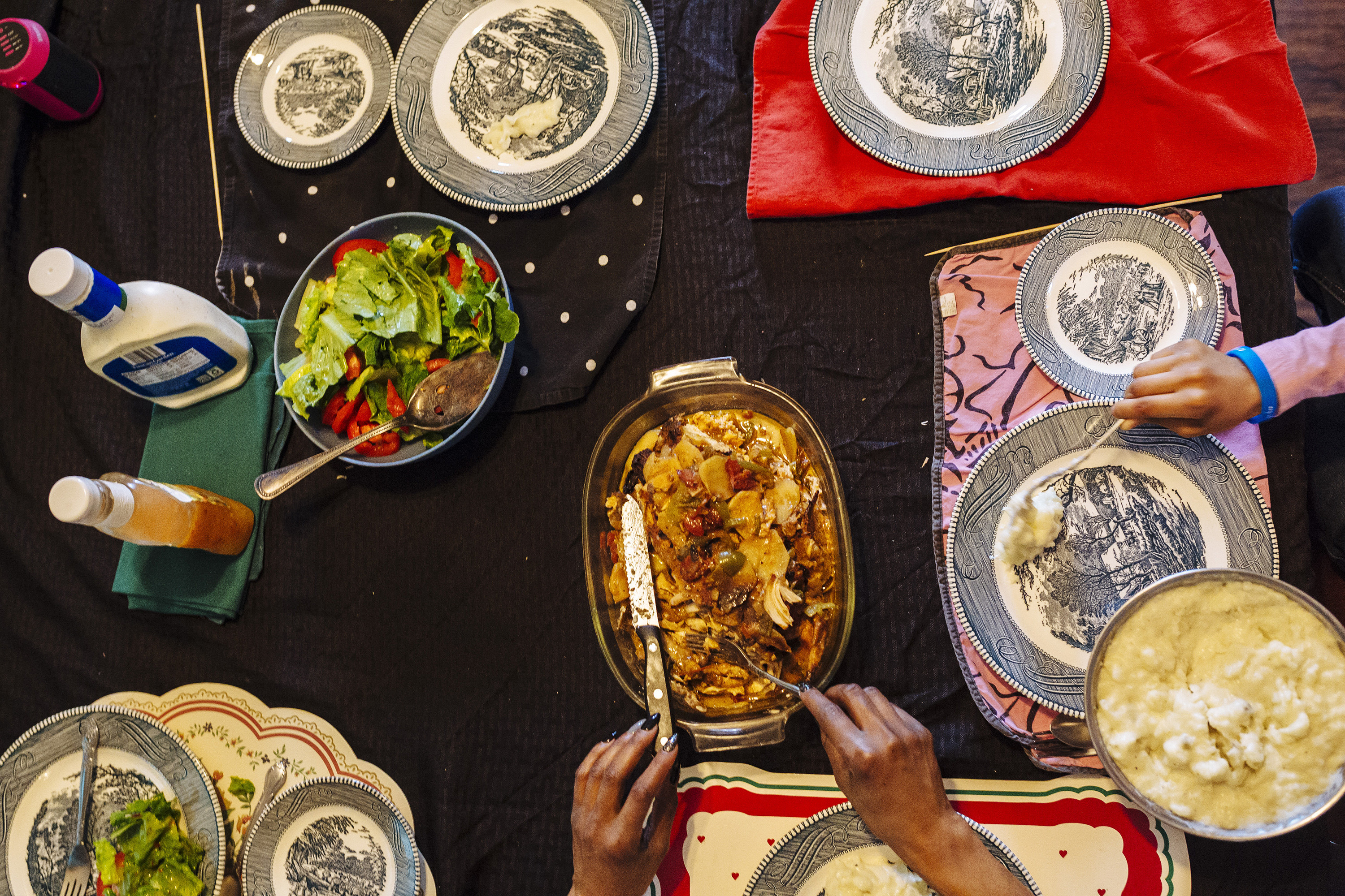 An overhead view of a tabletop covered in food dishes with hands reaching in to eat