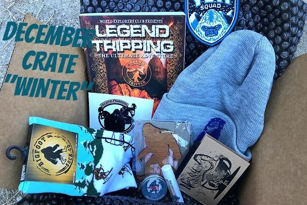 a Cryptid Crate box with a winter hat, pair of socks with bigfoot skiing on them, and other bigfoot themed items
