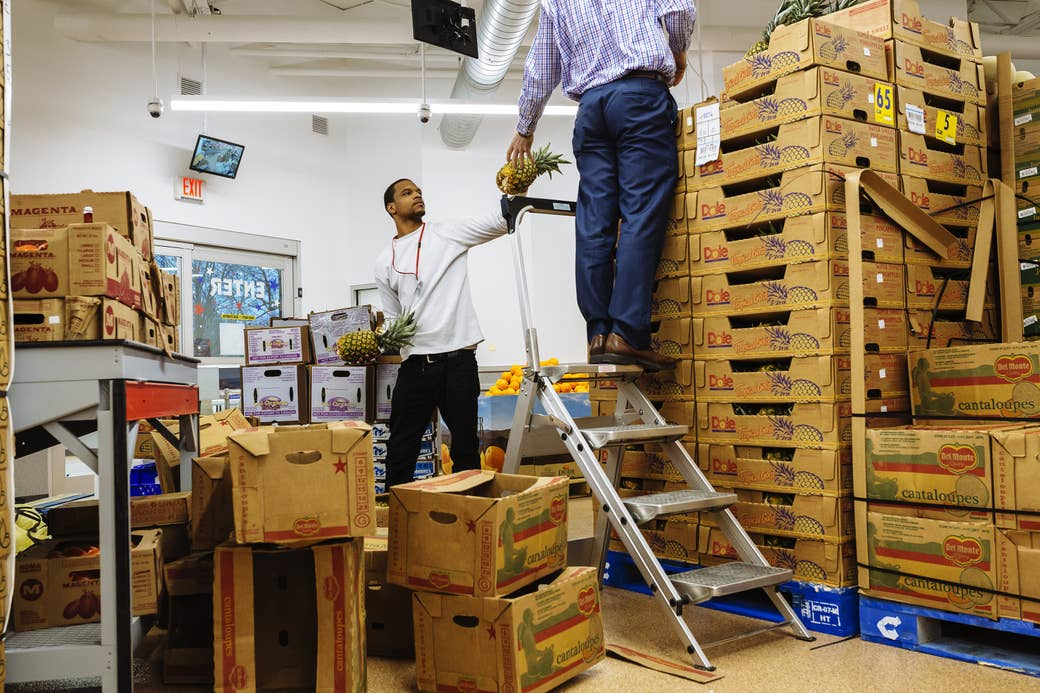 Two men in a grocery stockroom passing pineapples to each other