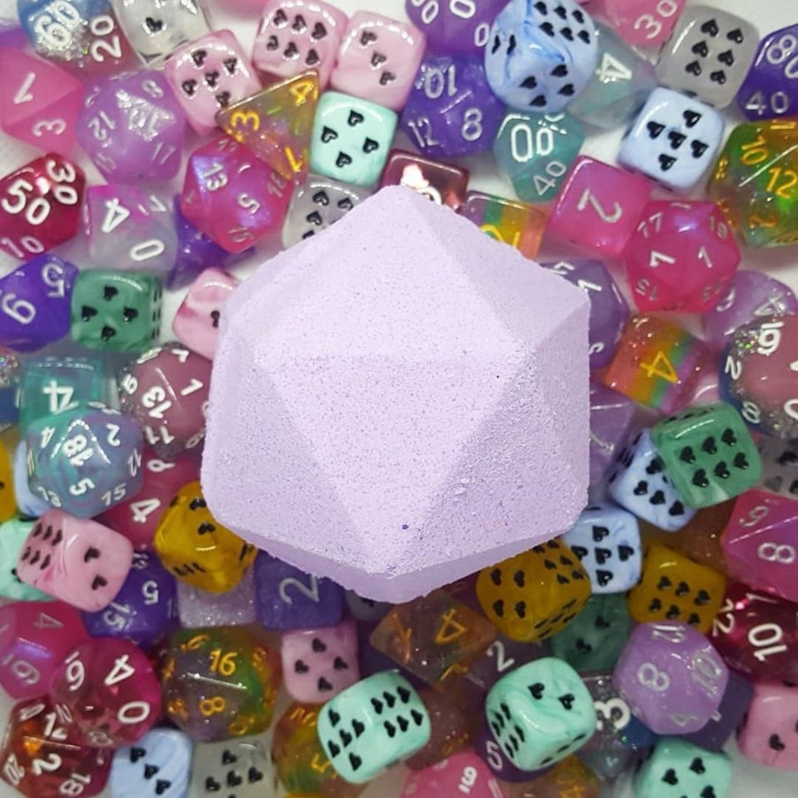 20-sided die bath bomb on pile of dice with various sides