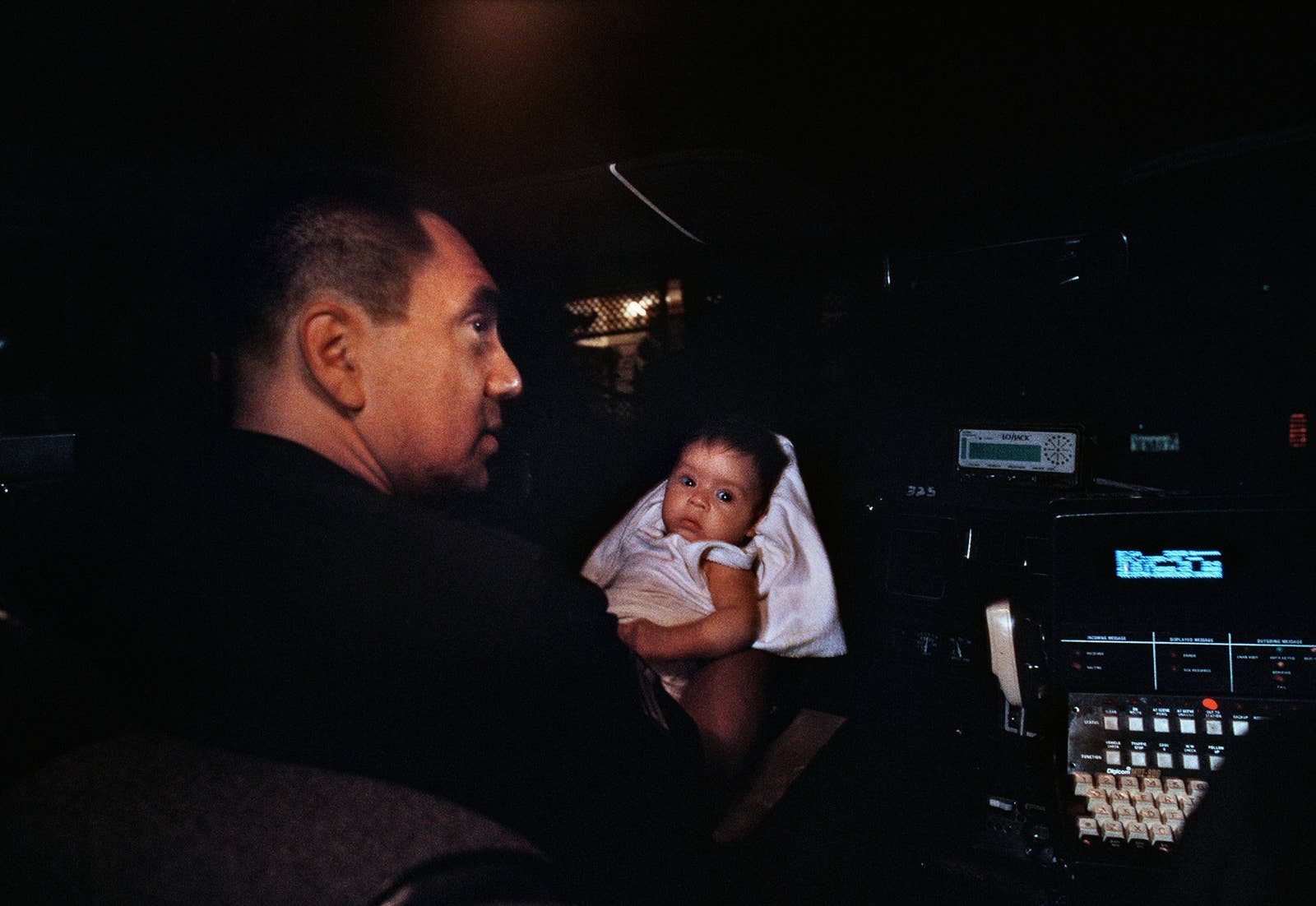 A cop holds a baby in a car at night