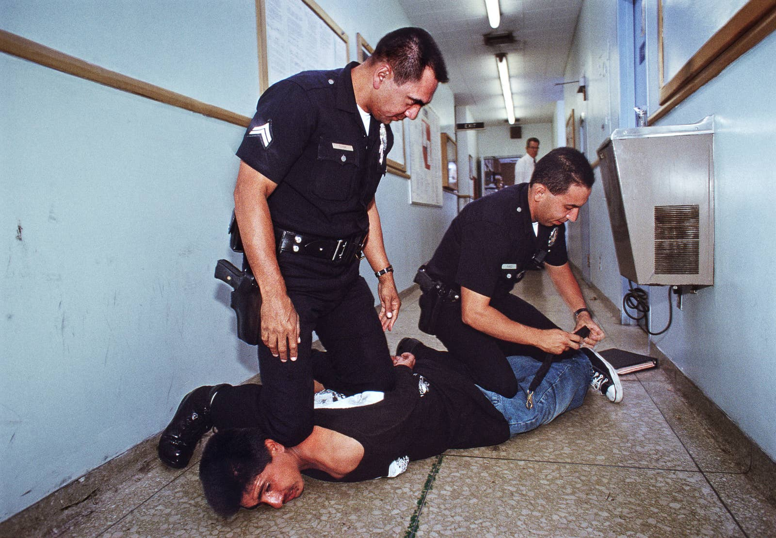 Two cops kneel on a guy in a hallway while adjusting some kind of strap