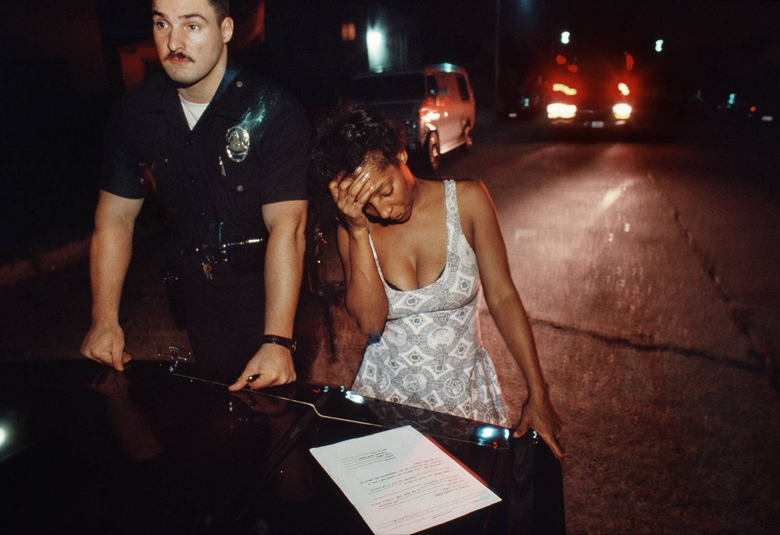 A woman holds her head in her hand while looking at a piece of paper on the trunk of a car while a police officer stands next to her and looks off into the distance
