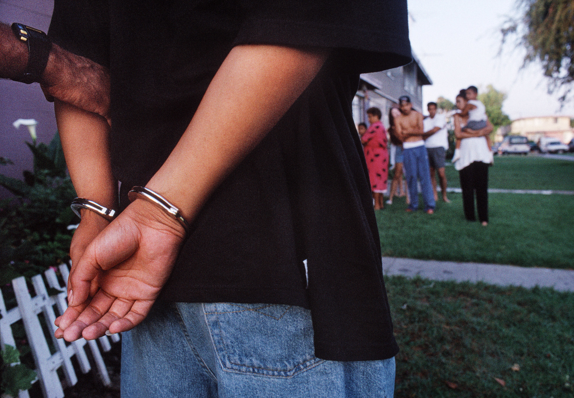A man in handcuffs is seen from behind while a family watches in the distance, out of focus