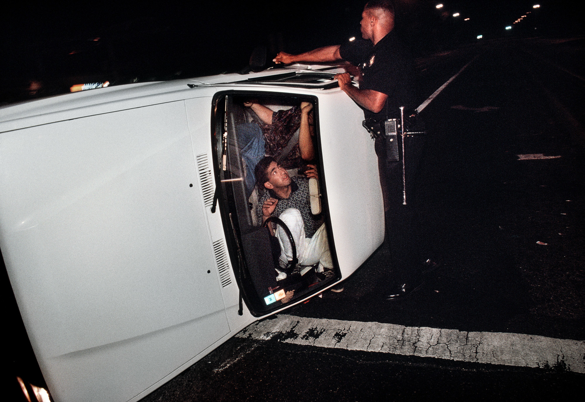 Two men are seen through the windshield of a car, which is laying on its side while a police officer tries to open the door