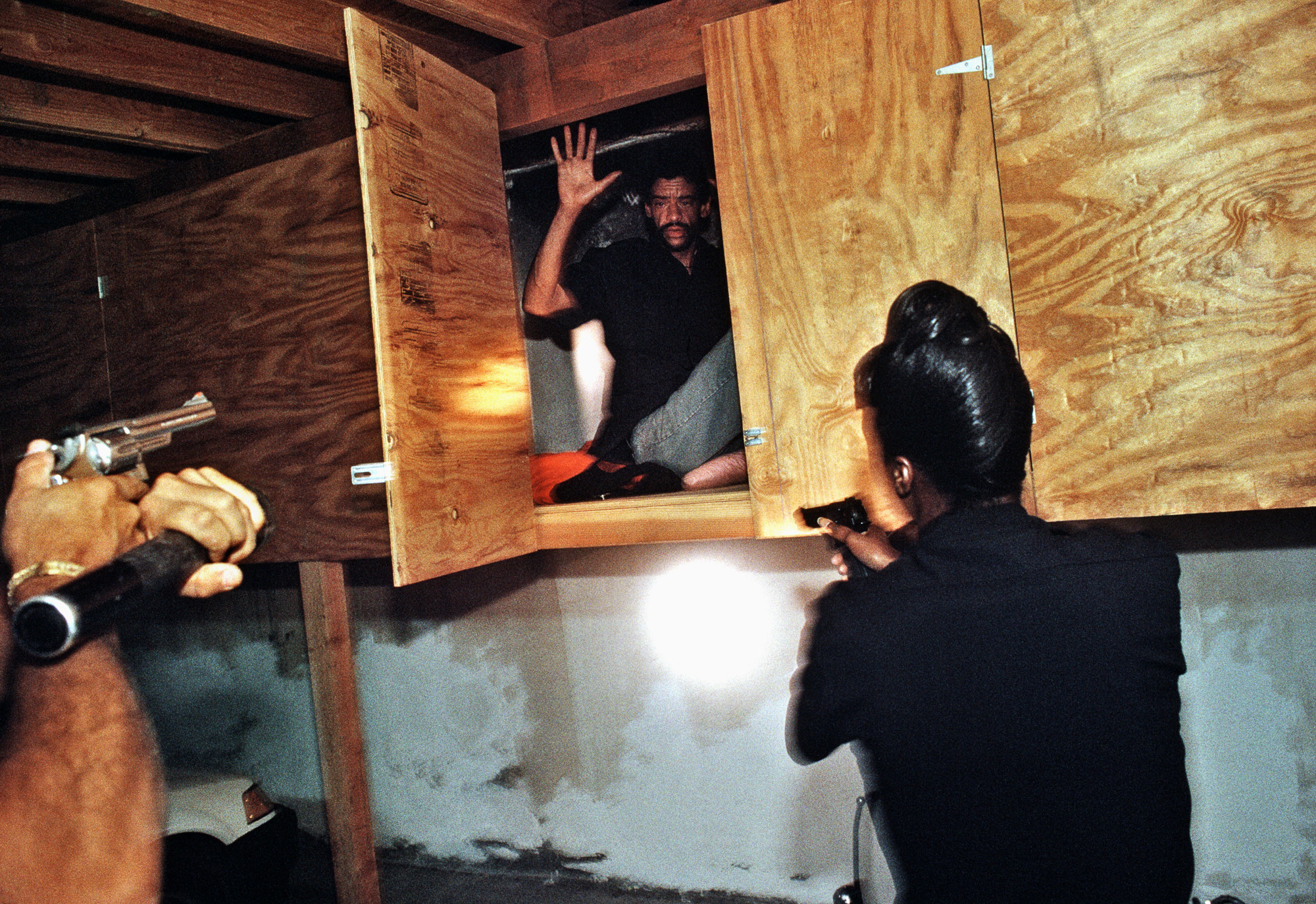 A man seen in a plywood cupboard with his hands up as two officers are seen from behind approaching with guns